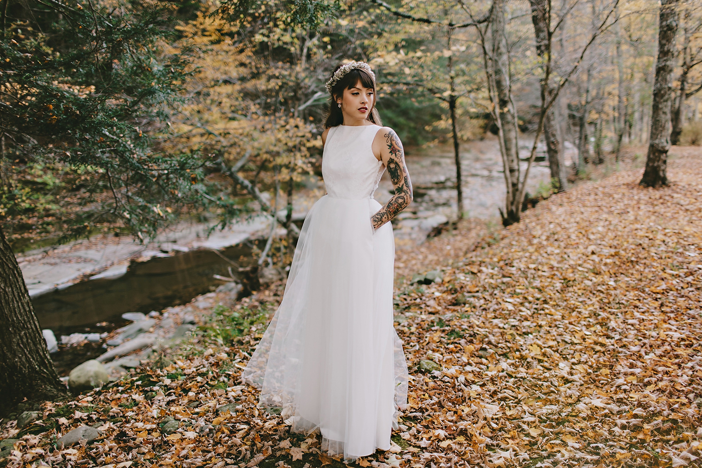 Bride in dress standing in leaves in upstate New York