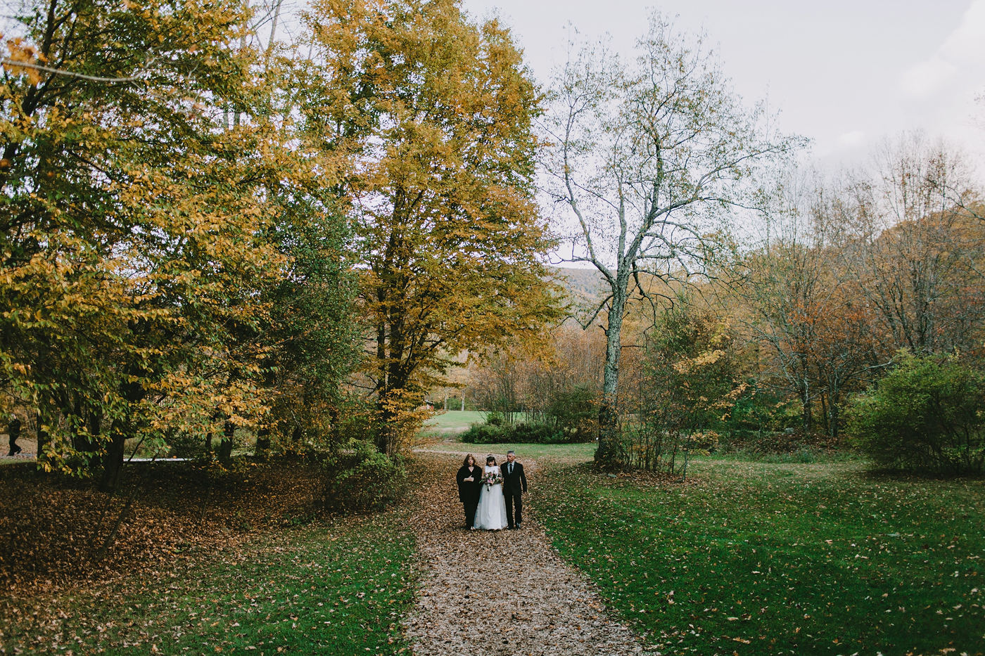 Bride walking down leaf covered path