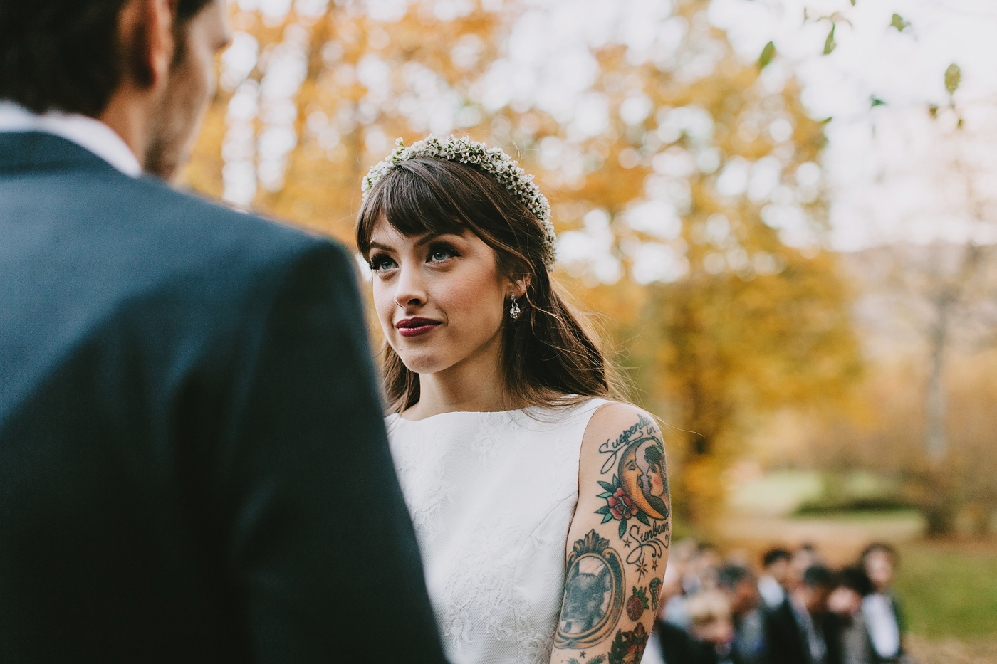 Beautiful tattooed bride looking into her grooms eye during their ceremony