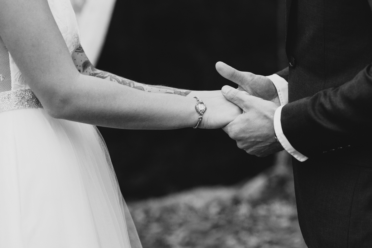 Black and white image of couple holding hands during their ceremony