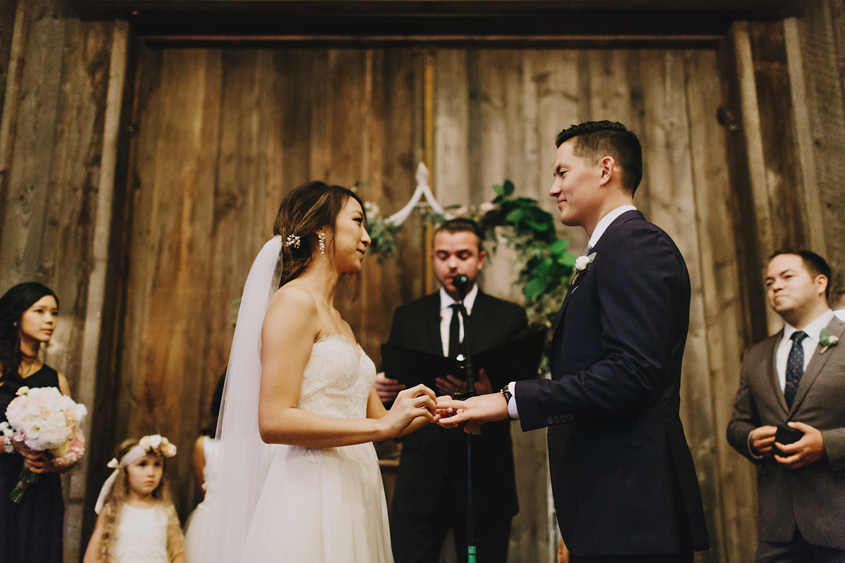 Bride puts ring on grooms hand during ceremony