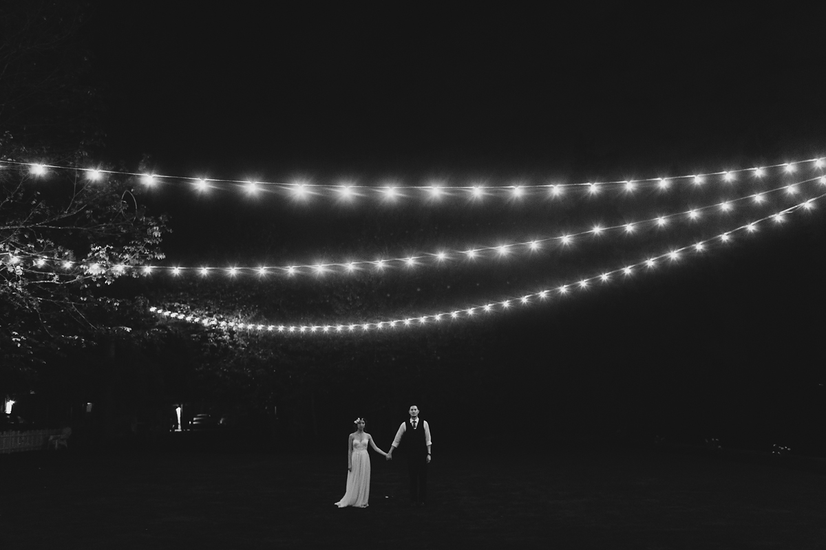 Newlyweds standing under light strands at night