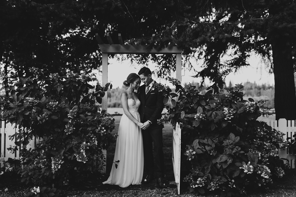 Couple standing in front of beautiful gate at their wedding