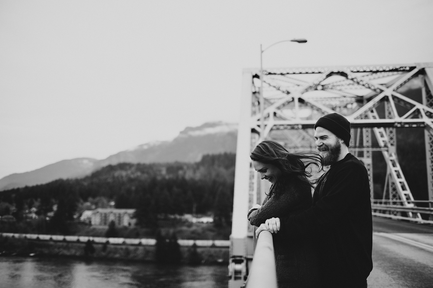 Couple laughing together on steel bridge