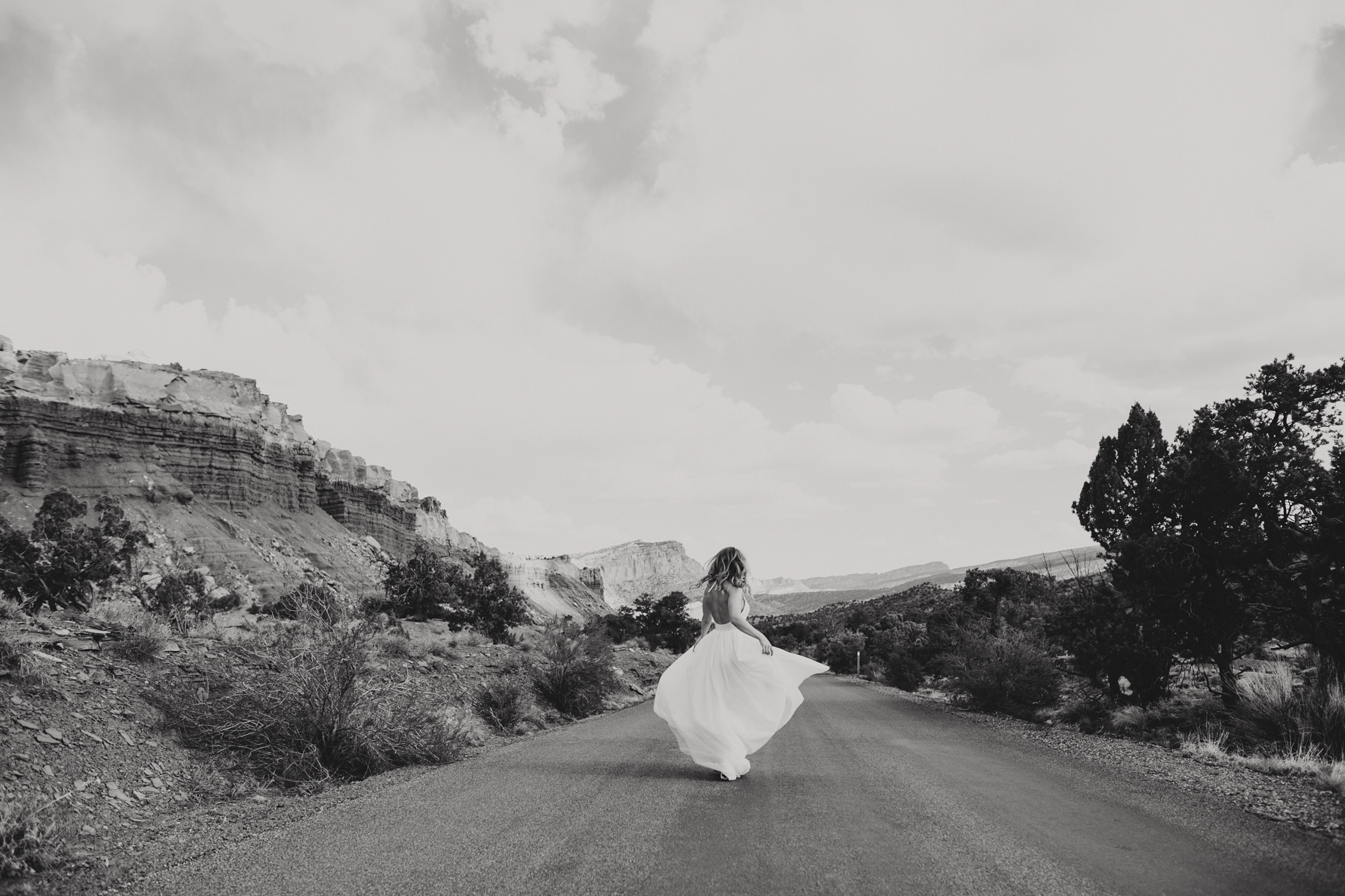 Bride spinning in middle of road wearing her wedding dress