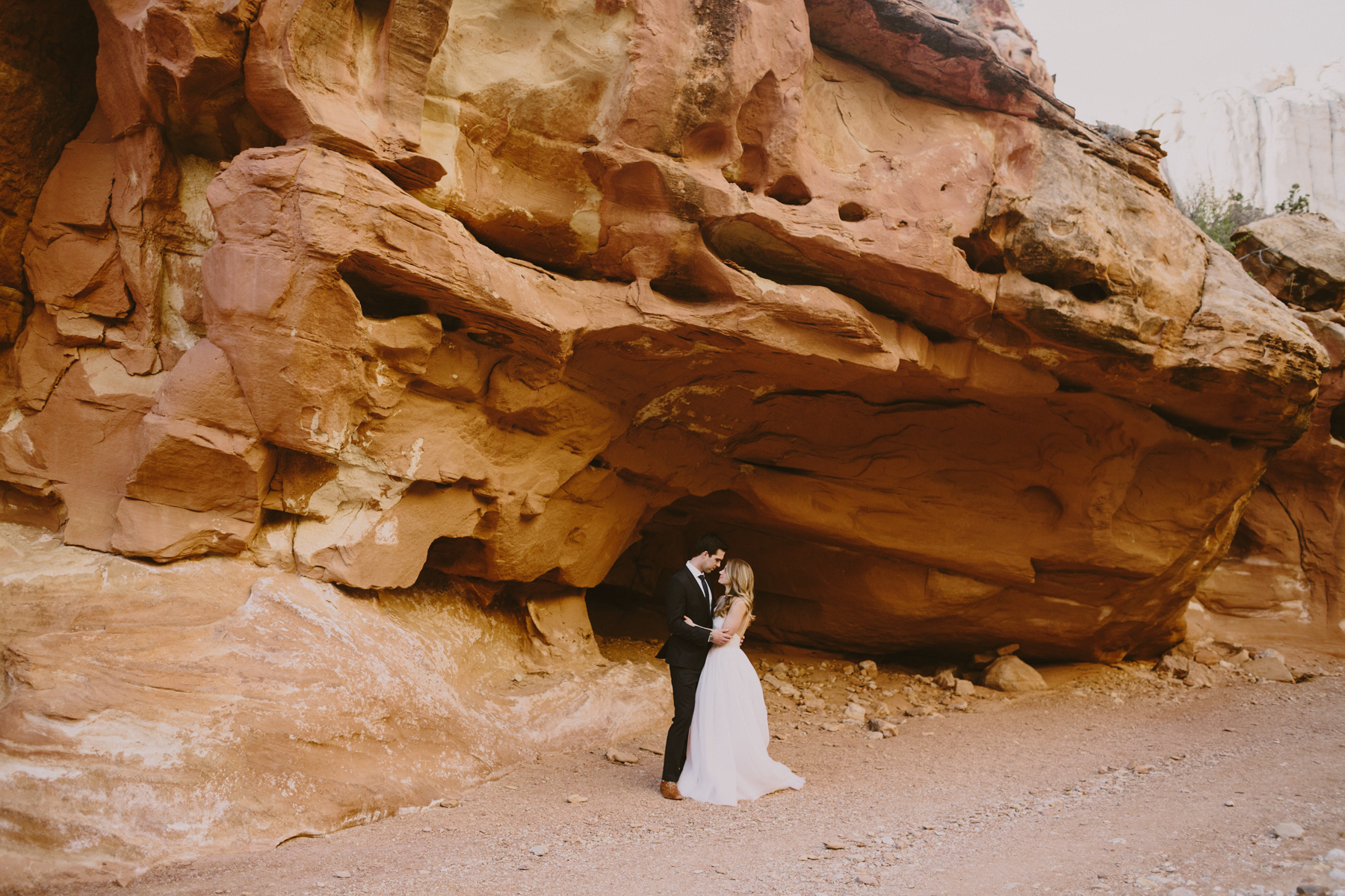 Sweet couple holding each other in one of southern utahs beautiful canyons
