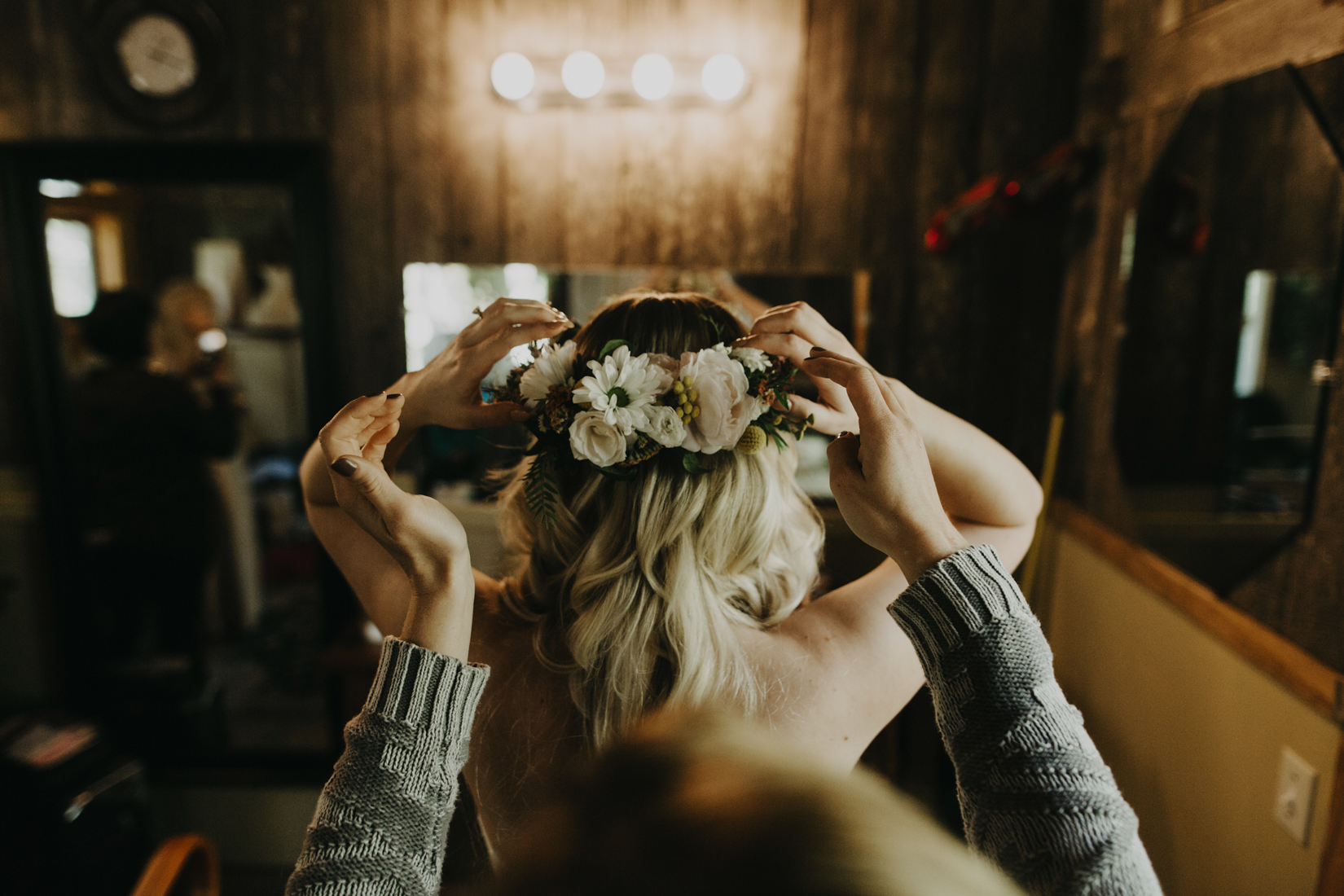 Bridesmaid helps bride adjust floral crown