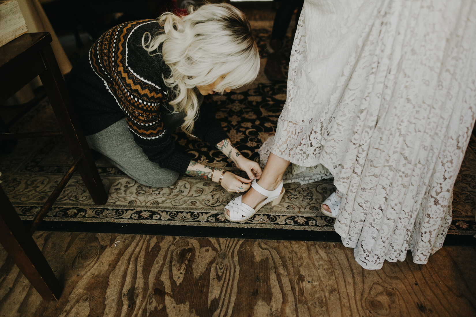 Bridesmaid helps bride with her shoes