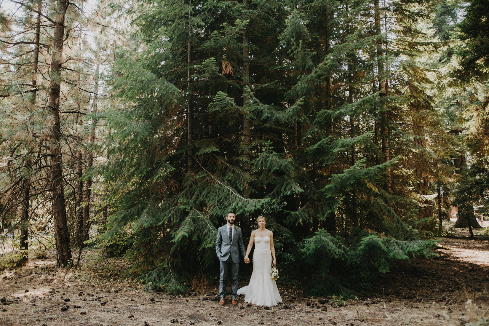 couple after their first look, standing hand in hand in a forest